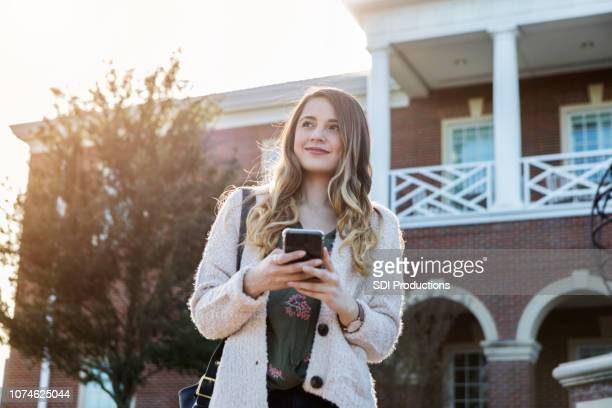 young woman uses phone while walking through college campus - college application stock photos and pictures