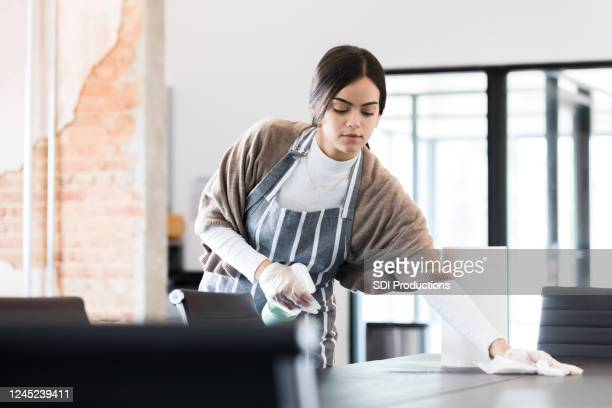 young woman uses protective gloves and disinfecting spray to clean - kitchen paper stock pictures, royalty-free photos & images