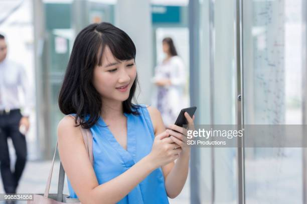 Young woman uses smartphone outside train station