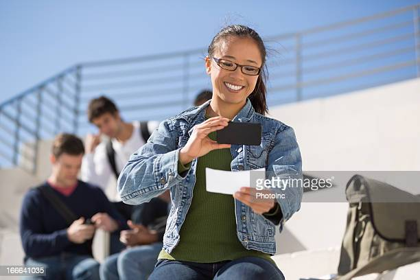 Young woman uses smartphone to deposit a check