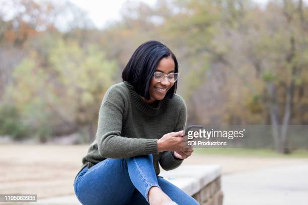 young woman uses smartphone while in park - free of charge stock pictures, royalty-free photos & images