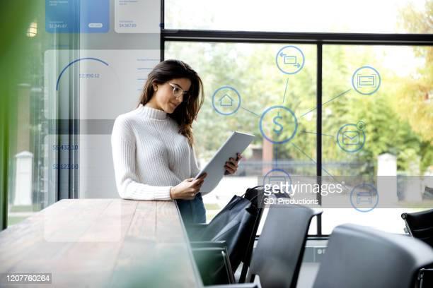 young woman uses tablet to check financial accounts - miglioramento digitale foto e immagini stock