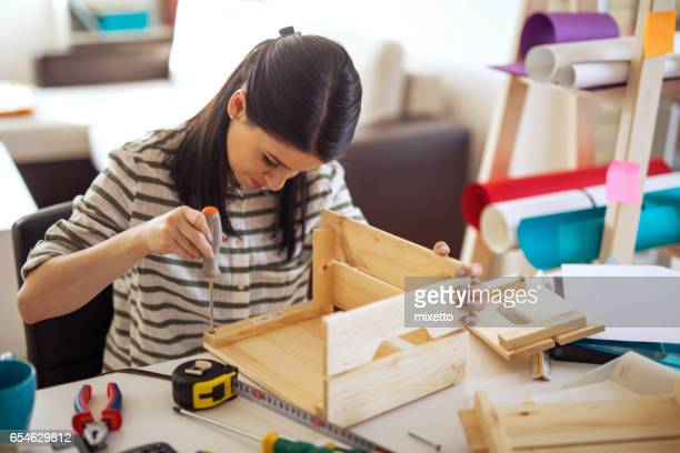 Young woman uses the screwdriver at home