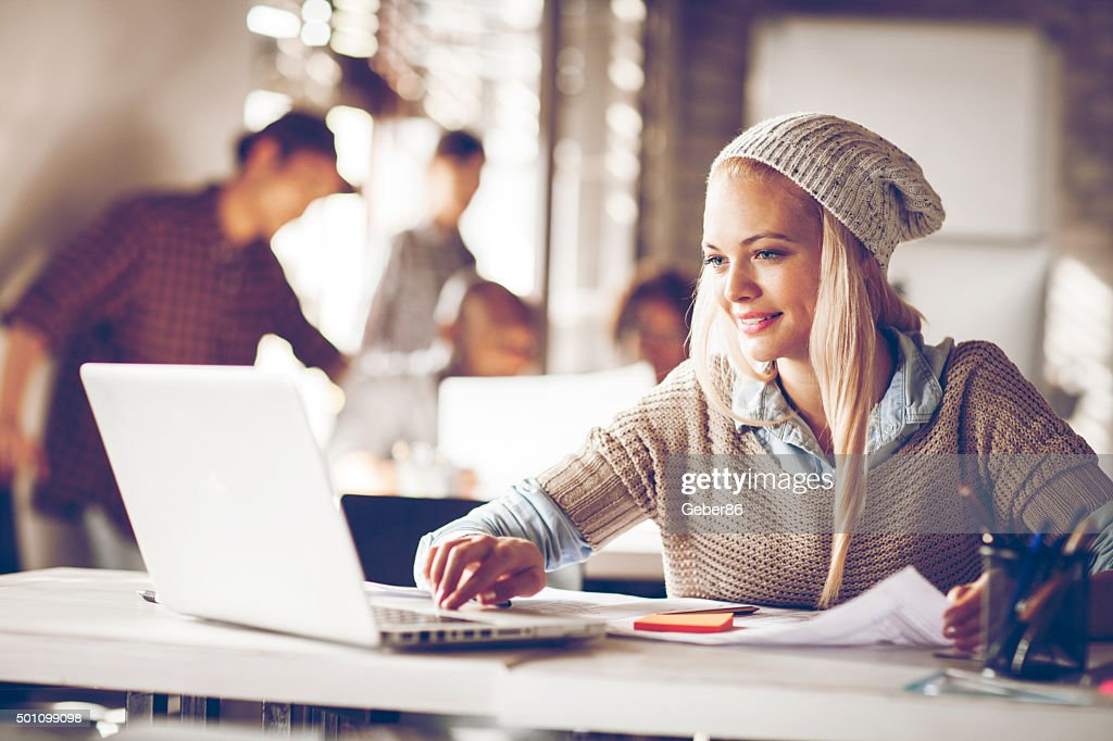 Young woman usign laptop in office : Stock Photo