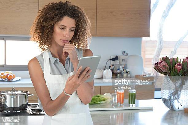 Young woman using a digital tablet in the kitchen