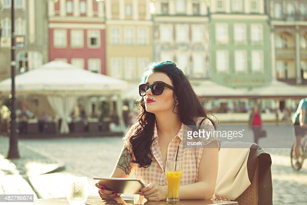 young woman using a digital tablet in the outdoor restaurant - izusek stock photos and pictures
