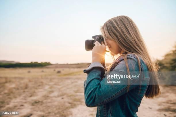 デジタル一眼レフ カメラを使用して若い女性