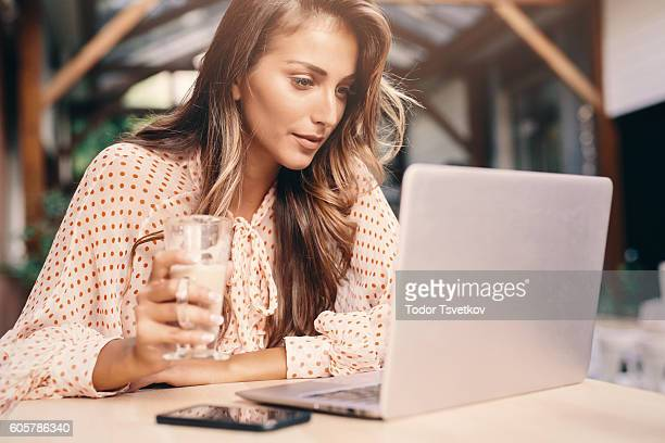 young woman using a laptop at the cafe - curiosity stock pictures, royalty-free photos & images