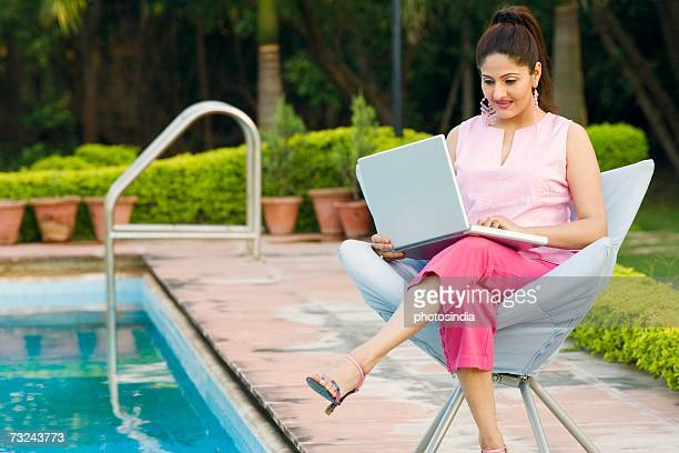 young woman using a laptop at the poolside - 短めのパンツ ストックフォトと画像
