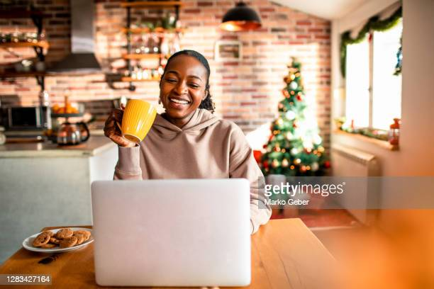 young woman using a laptop during christmas - 在宅勤務 ストックフォトと画像