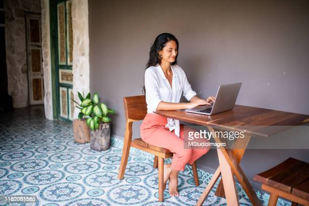 young woman using a laptop - cross legged stock pictures, royalty-free photos & images