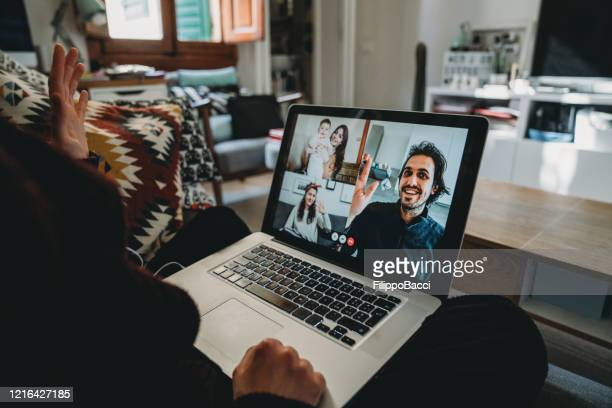 young woman using a laptop to connect with her friends and parents during quarantine - facetime stock pictures, royalty-free photos & images