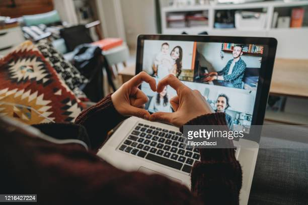 young woman using a laptop to connect with her friends and parents during quarantine - social distancing stock pictures, royalty-free photos & images