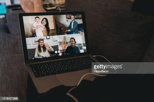 検疫中に彼女の友人や両親と接続するためにラップトップを使用して若い女性 - 外出禁止令 ストックフォトと画像