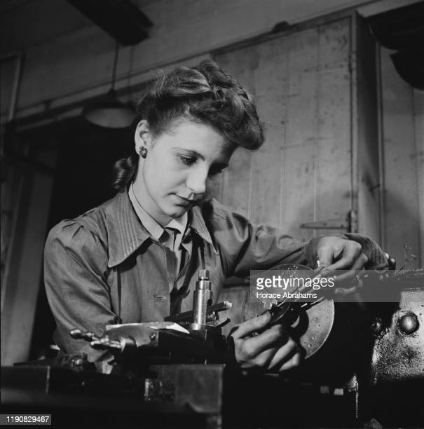 A young woman using a micrometer during her training for war work in the machine shop of the Ministry of Labour training centre at Chelsea...