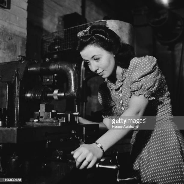 A young woman using a milling machine during her training for war work in the machine shop of the Ministry of Labour training centre at Chelsea...