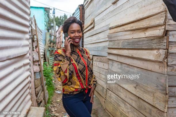 jonge vrouw met behulp van een mobiele telefoon in een afrikaanse township - gemeente stockfoto's en -beelden