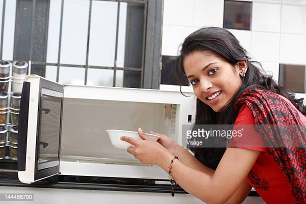A young woman using a oven
