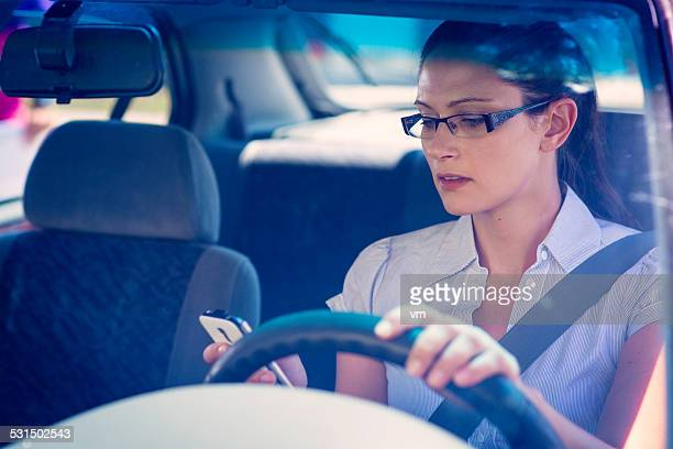 Young Woman Using a Phone While Driving a Car