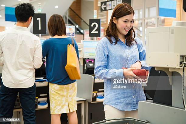 Young woman using a self checkout machine in the supermarket