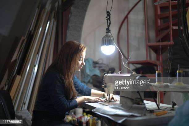 布張りのワークショップでミシンを使用する若い女性 - 裁縫道具 ストックフォトと画像