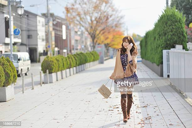 young woman using a smartphone in the city - japanese short skirts stock pictures, royalty-free photos & images