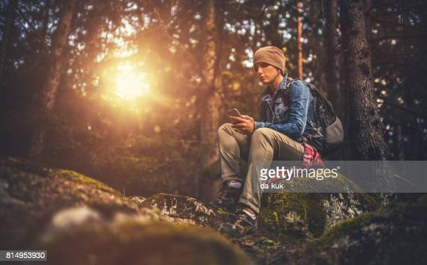 Young woman using a smartphone in the forest