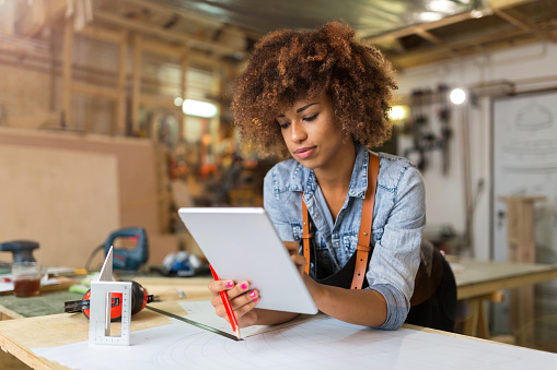 Young woman using a tablet in her workshop 973301656