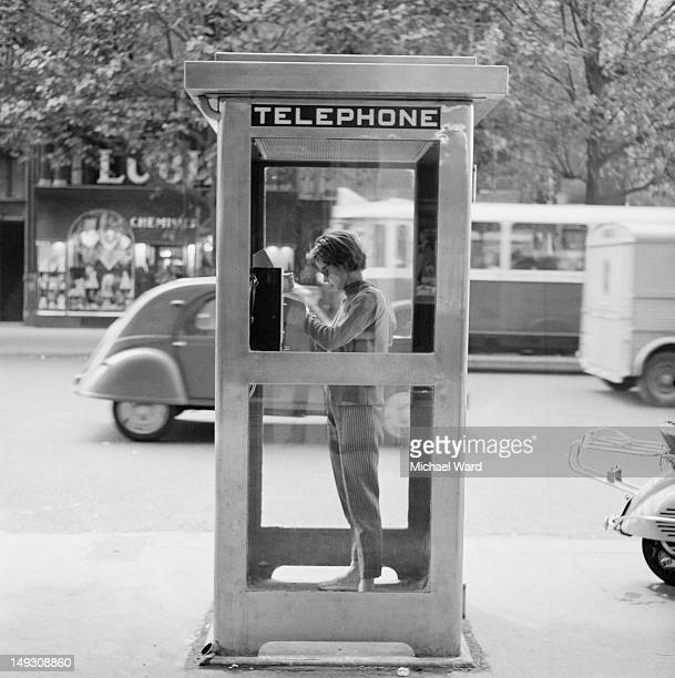 A young woman using a telephone booth in Paris 1959