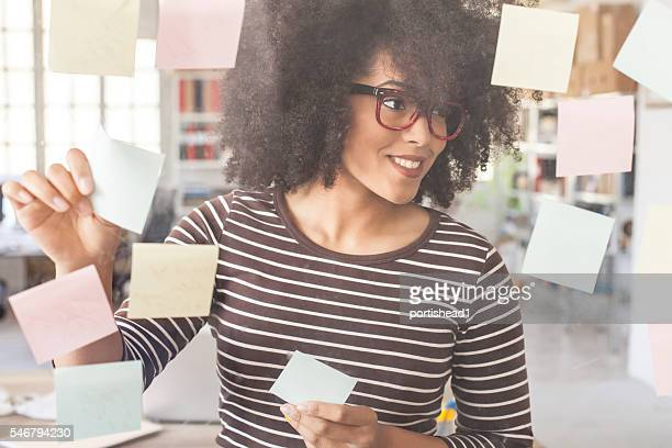 Young woman using adhesive notes in modern office