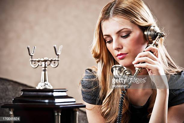 Young woman using an antique phone.