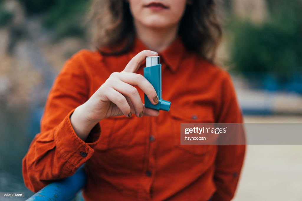 Young woman using an asthma inhaler outdoors : Stock Photo