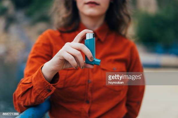 Young woman using an asthma inhaler outdoors