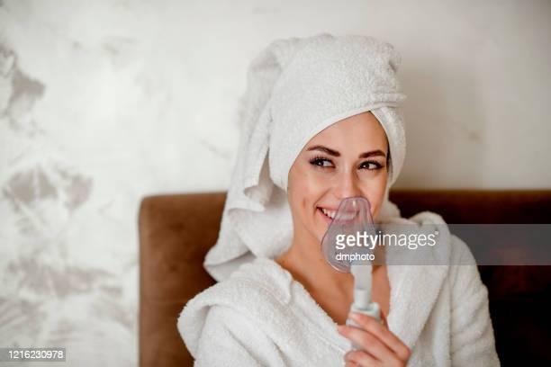 young woman using an asthma inhaler - amigdalite imagens e fotografias de stock