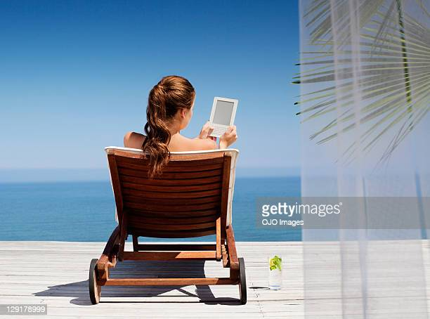 Young woman using an electronic reader while sitting on deck chair