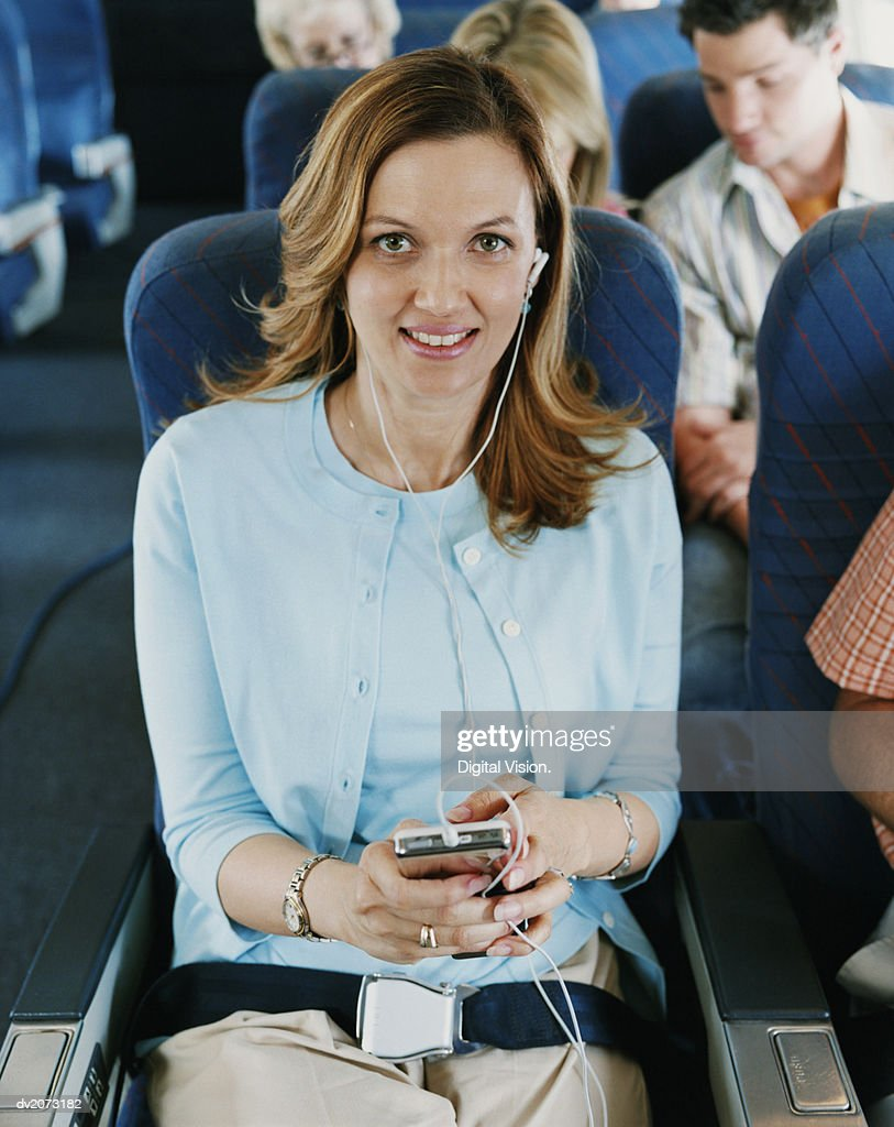 Young Woman Using an MP3 Player on a Plane : Stock Photo