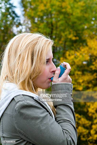 Young Woman Using As Asthma Inhaler Outdoors
