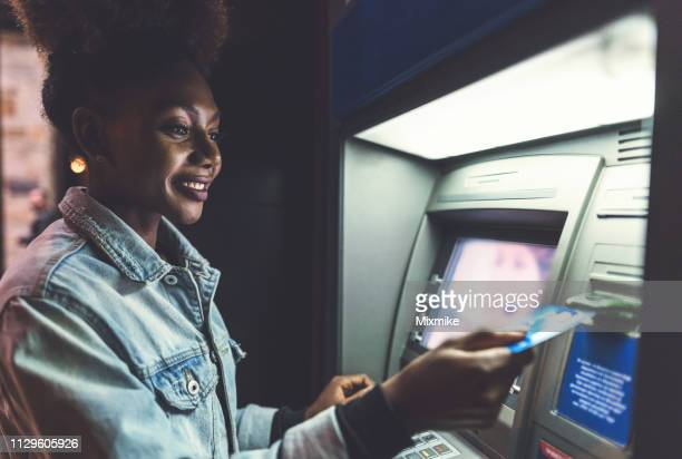 young woman using atm device on the street - atm stock pictures, royalty-free photos & images