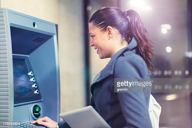 Young woman using ATM machine at night