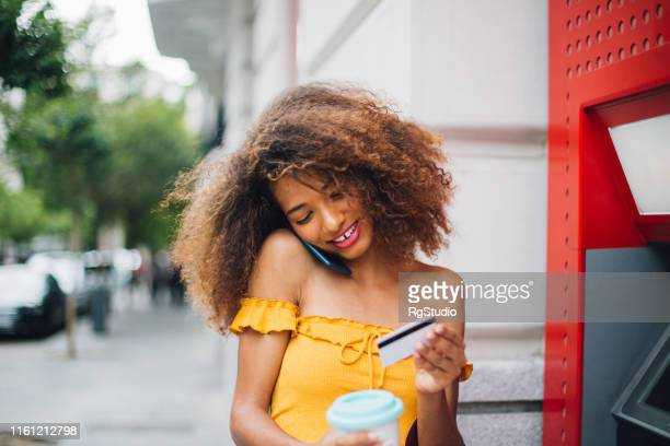 young woman using atm - bank account stock pictures, royalty-free photos & images