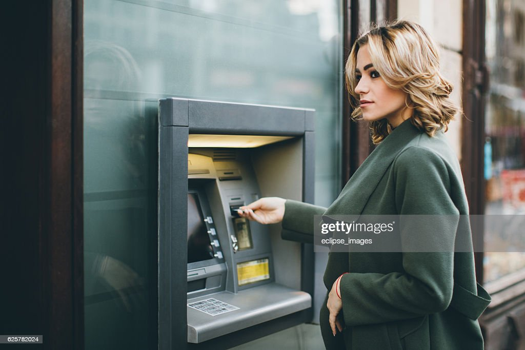 Young woman using ATM : Stock Photo