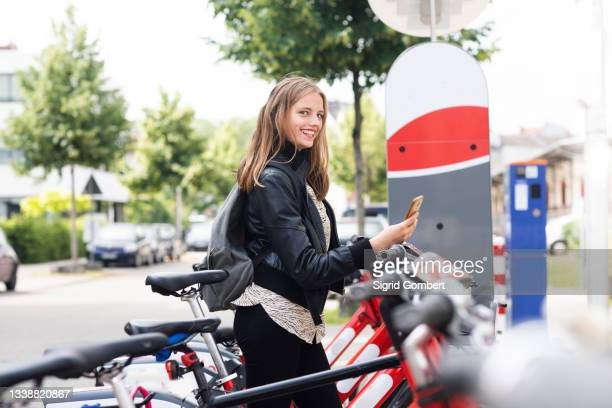 young woman using bike sharing system - sigrid gombert stock pictures, royalty-free photos & images