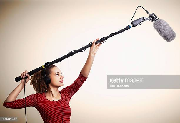 young woman using boom microphone and headphones  - film crew stock pictures, royalty-free photos & images