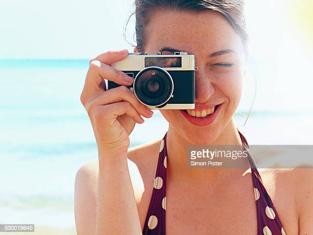 Young woman using camera on beach
