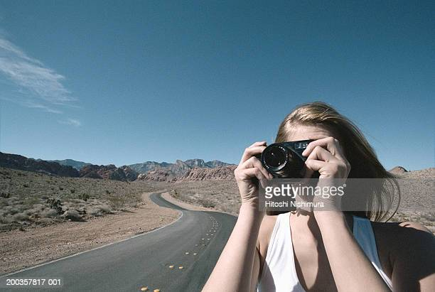 Young woman using camera on road side, close up