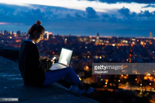 young woman using cell phone and laptop at dawn above the city, barcelona, spain - コンピュータ機器 ストックフォトと画像