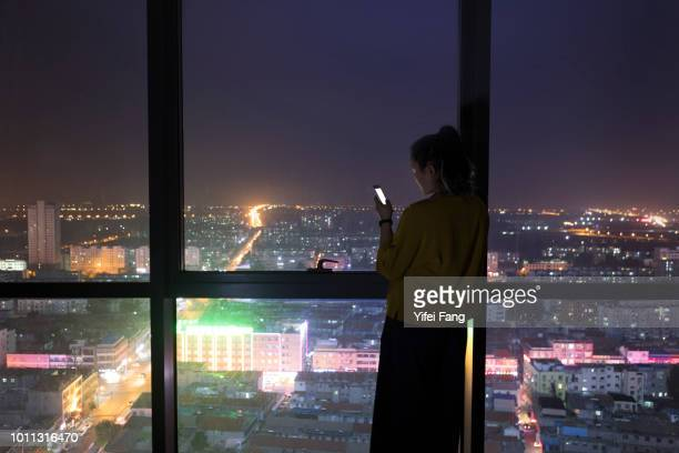 young woman using cell phone in front of city nightscape - front view ストックフォトと画像
