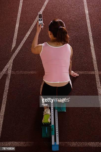 young woman using cell phone in starting block - sprint sport wettbewerbsform stock-fotos und bilder