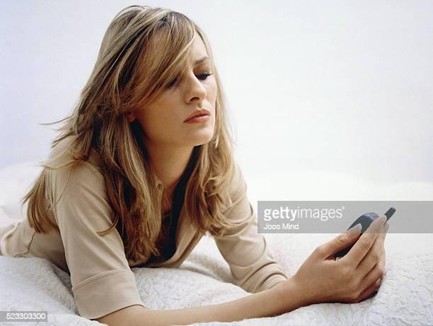 young woman using cell phone on bed - ongeduldig stockfoto's en -beelden
