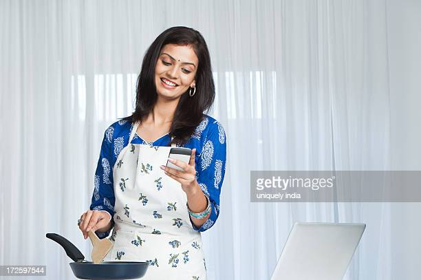 Young woman using cell phone while cooking